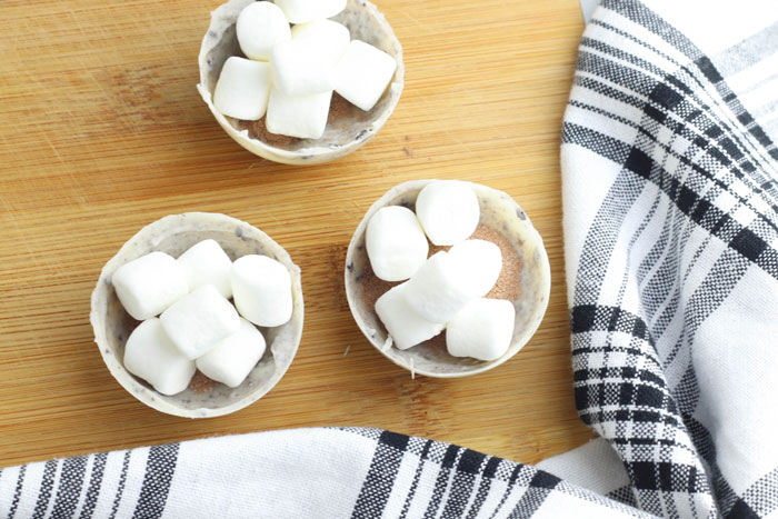 mini marshmallows and instant hot cocoa powder in the shell of a oreo cookie hot cocoa bomb ready for the top to go on