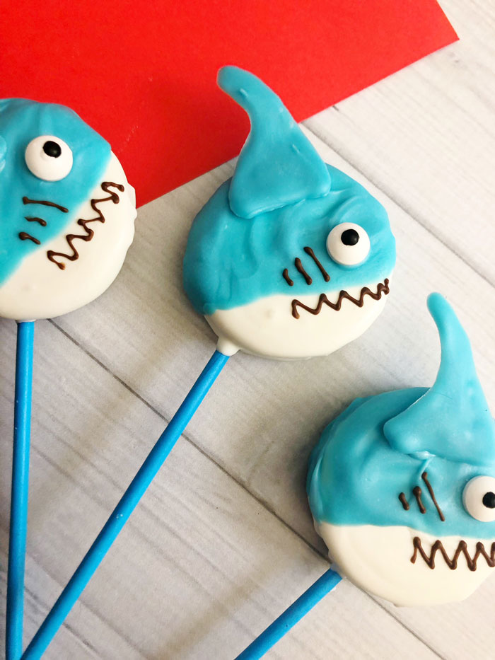 shark party treats, oreo cookies coated in blue and white candy decorated to look like sharks