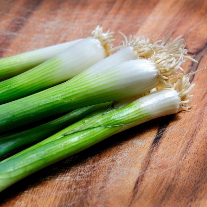 pile of spring onions with the ends on set on a wooden work top ready for cooking with in April and throughout the summer