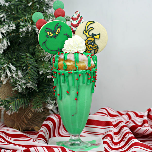 how the grinch stole christmas dessert of a freakshake style. with cookies, donuts, brownies and more in a tall glass ideal to share in front of a mini christmas tree on top of a red and white cloth