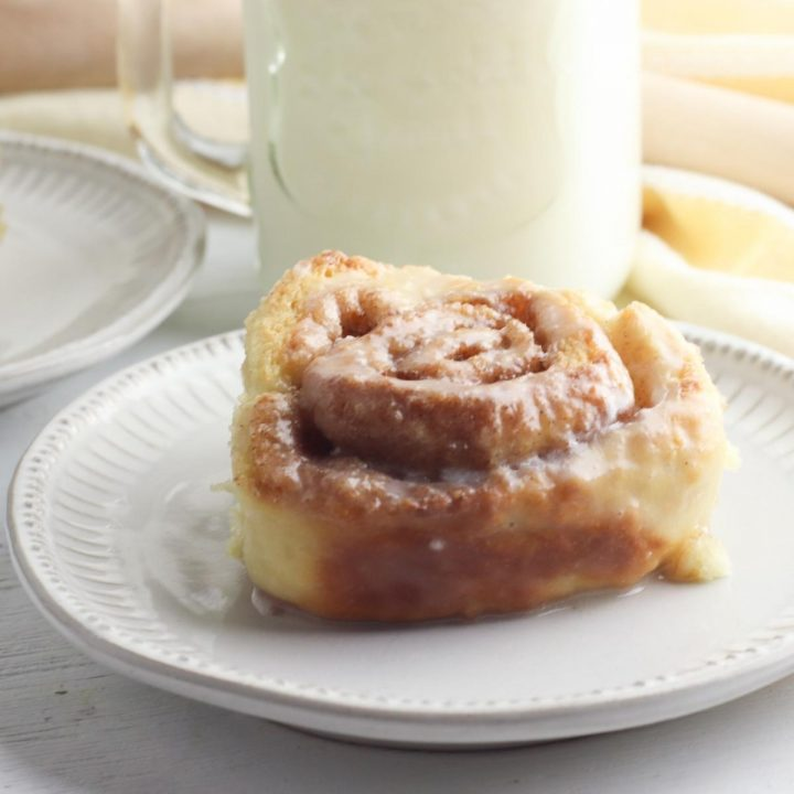 homemade sticky cinnamon roll on a white plate with a glass of cold milk behind
