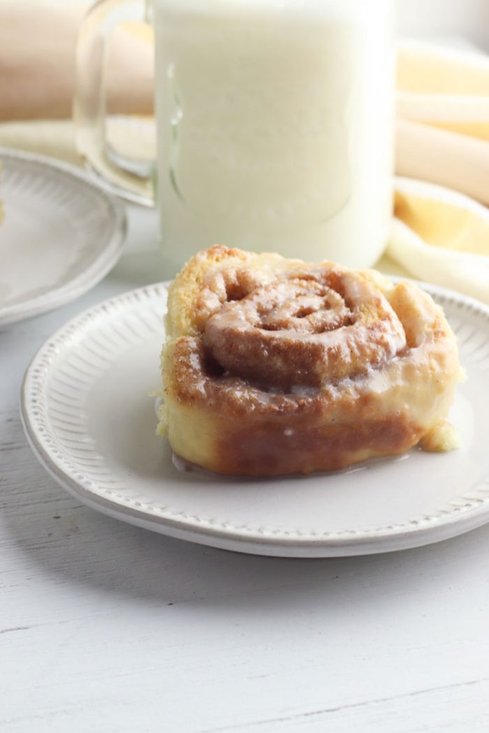 plate with a single cinnamon roll covered in homemade icing infront of a glass of milk