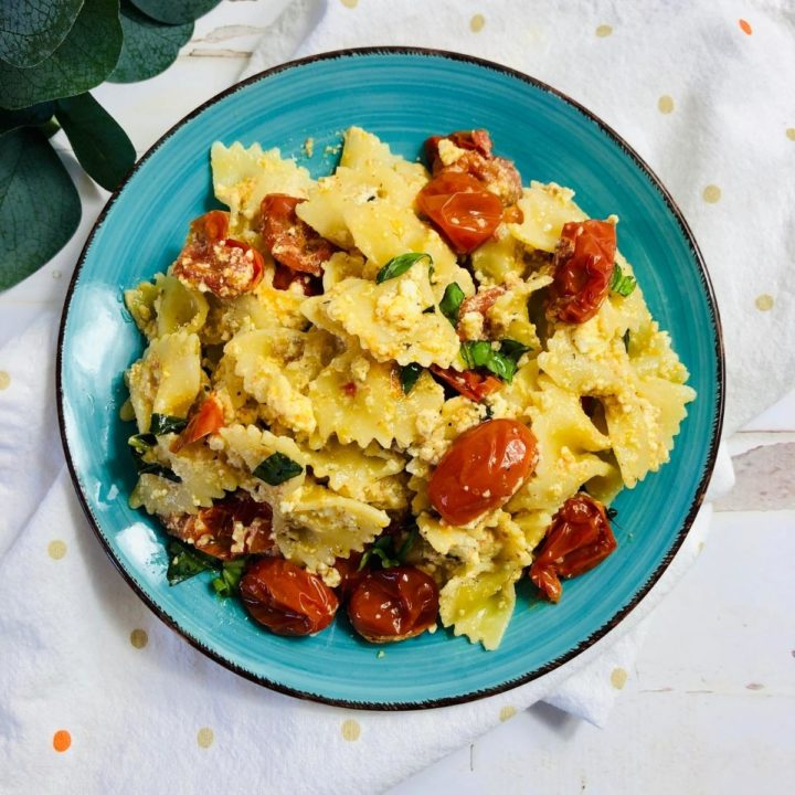 baked feta and mini plum tomato pasta on a dish with fresh basil shown. The dish in place on a white table cloth ready for family dinner