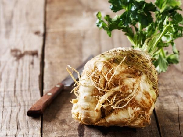 a celeriac rooot with green top on a wooden table with a knife beside ready to be chopped up