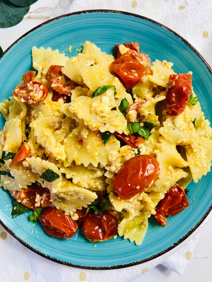 feta and tomato pasta with fresh basil on a blue plate