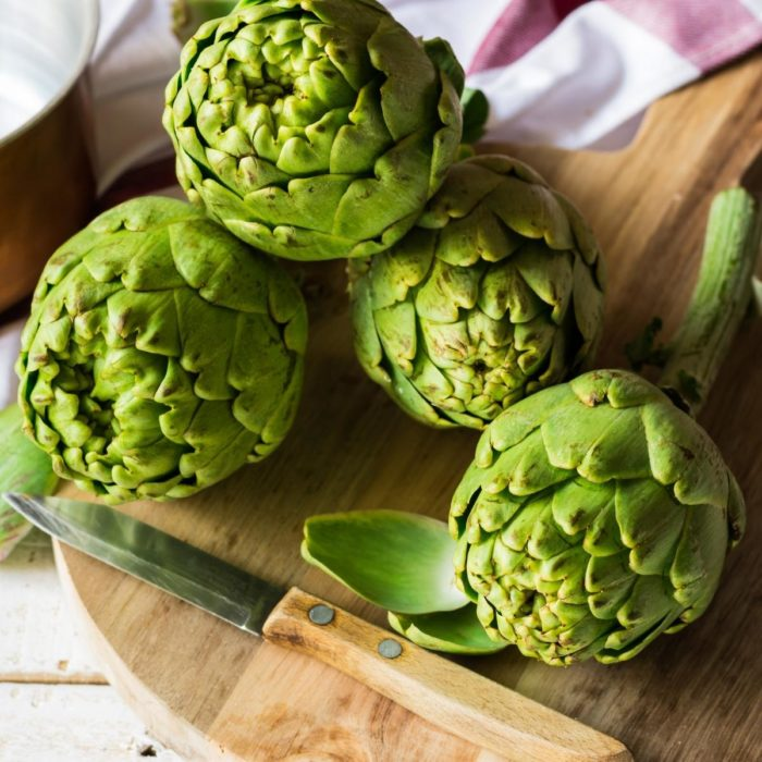 4 artichoke hearts on the kitchen table with a knife ready to be prepared to cook