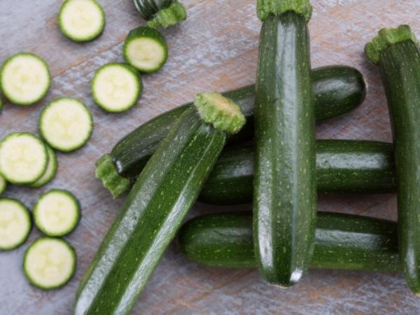 6 zucchinis on a wooden work top with slices of the zucchini beside it