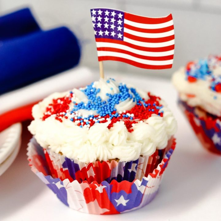 strawberry cupcakes decorated with white butter cream and red and blue sprinkles in red, white and blue cupcake liners a USA flag in the middle all on a white table with a set of red, white and blue napkins beside ready for independence day party