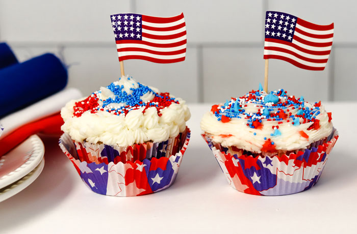 finished cupcakes ready for the independence day party with red and blue sprinkles on white buttercream and little flags in the center