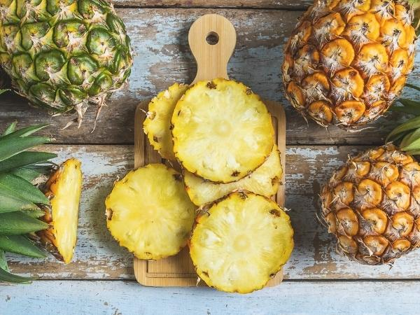 sliced pineapple in the centre of the image on a wooden chopping board, around the edge are 3 further pineapples plus the top of the chopped up on.