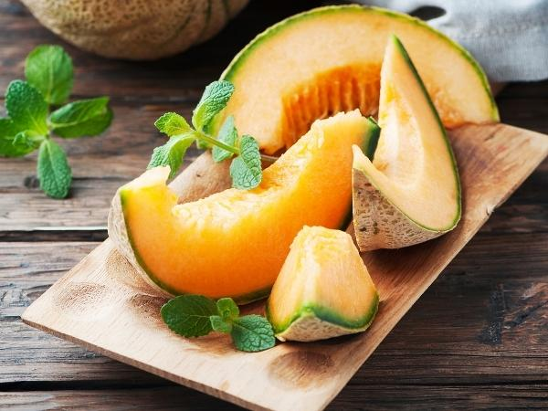 slices of canataloupe melon with seeds removed on a wooden chopping board. Mint is placed as a garnish on the melon