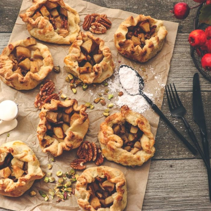 delicious fall dessert flat lay with homemade apple and pecan rustic pies on greaseproof paper and with icing sugar ready to sprinkle on top