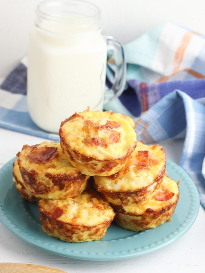 breakfast muffins on a plate with a jug of cold milk behind on a table with a tea towel