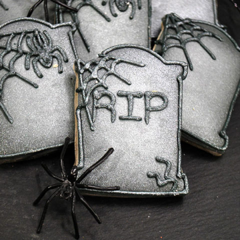 Fun Halloween Tombstone Cookies with RIP, on a black table with a spider