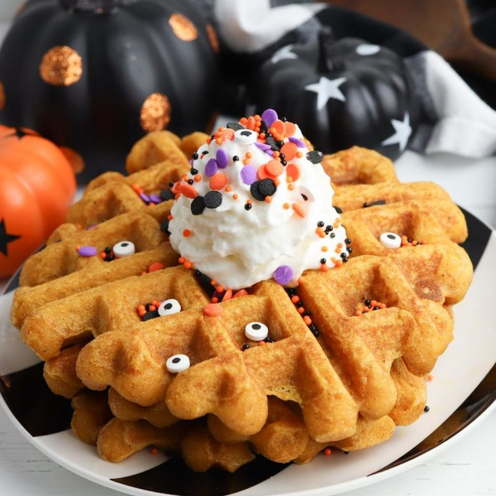 a stack of halloween Belgian waffles with whipped cream and candy eyes and sprinkles with pumpkins behind ready for dessert for the kids