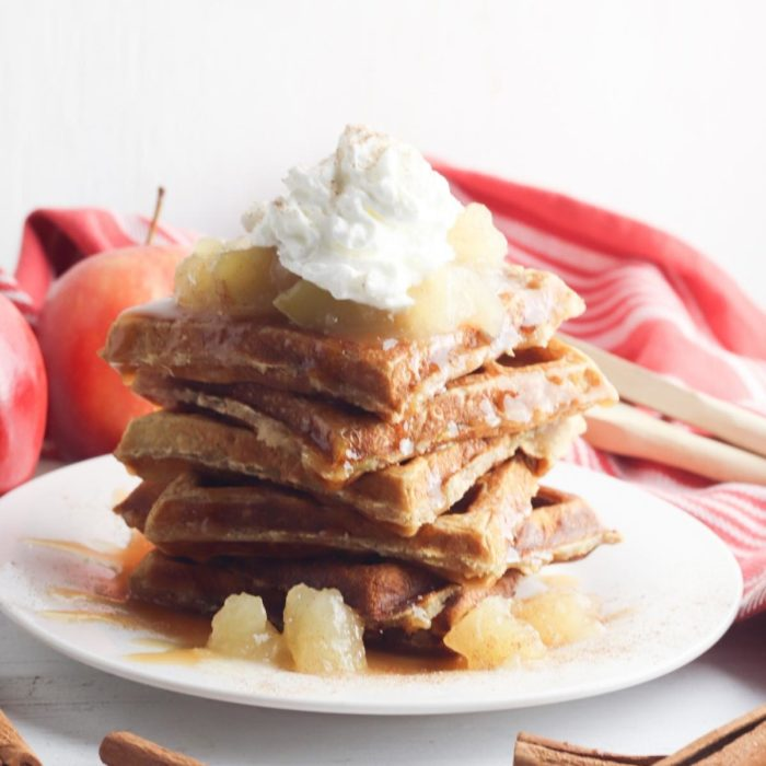 a stack of apple and cinnamon waffles on a white plate with apple pie filling caramel syrup and whipped cream, a delicious fall dessert for the family to enjoy