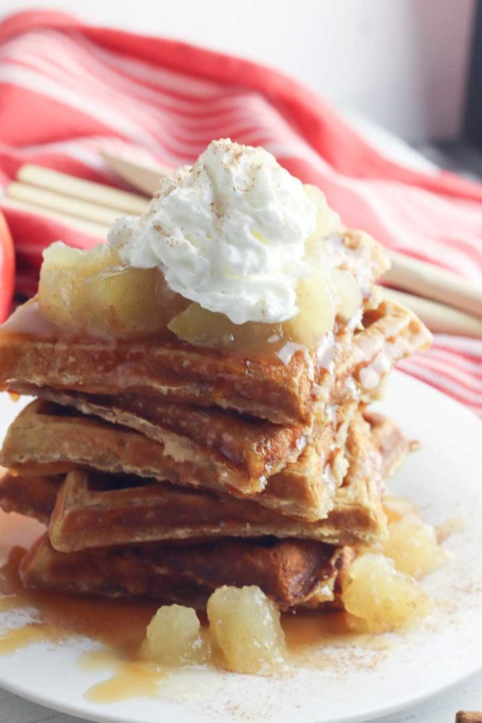 a stack of delicious dessert waffles made with freshly grated apples and cinnamon pilled high and topped with apple pie filling, caramel syrup and whipped cream