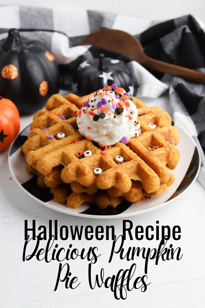 Halloween recipe for delicious pumpkin pie waffles Pinterest image with a stack of the waffles on a plate with sprinkles, eyes and whipped cream with pumpkins behind