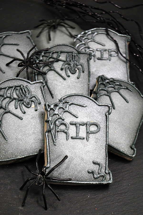 tombstone halloween cookies to make and decorate a set with spider webs and RIP in royal icing on the front