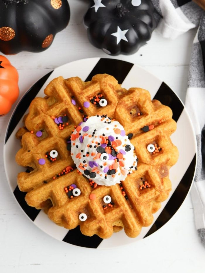 top down view of a stack of Halloween Belgian Waffles with candy eyes and whipped cream with orange, purple and black halloween sprinkles. A fun dessert for kids before trick or treating