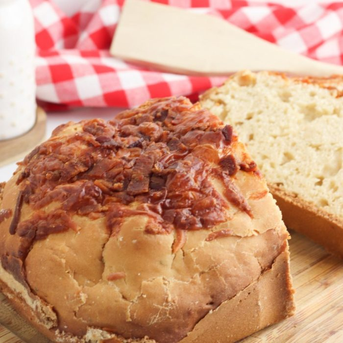 loaf of bacon and cheese bread from the brad machine on a wooden chopping board sliced and ready for butter