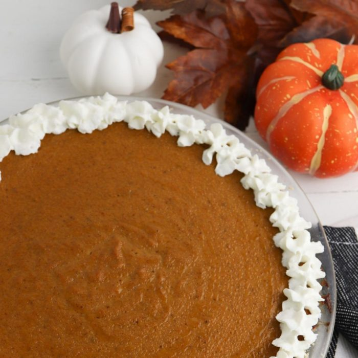 top down view of a simple homemade pumpkin pie on the table for thanksgiving with fall leaves and mini pumpkins and squash