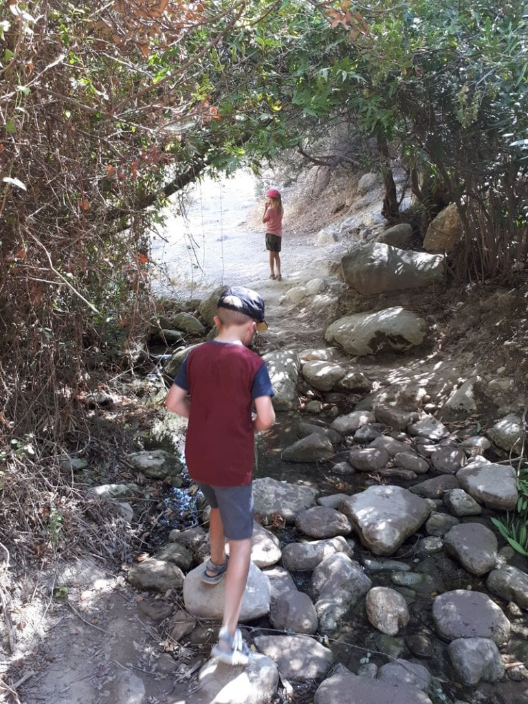 kids crossing the stream at the bottom of the avakas gorge that formed the amazing natural wonder on Cyprus