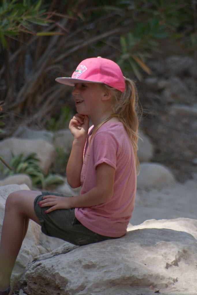 girl sitting on a rock in the Avakas Gorge after taking part of the trail