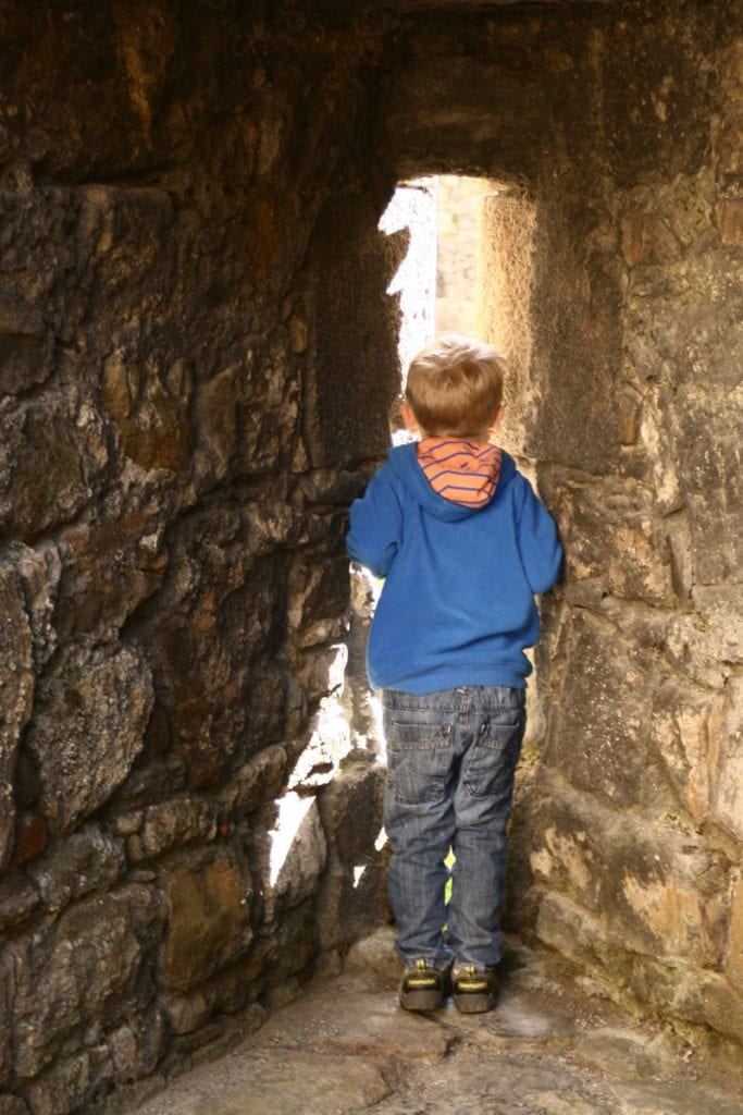 child looking through the arrow slits out of the castle walls at Beaumaris Castle North Wales
