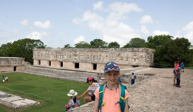 child on the top of the staircase at the nunnery quadrangle in Uxmal