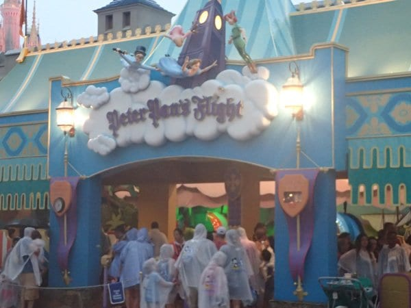 people queuing up for the peter pan ride in the magic kingdom in the rain