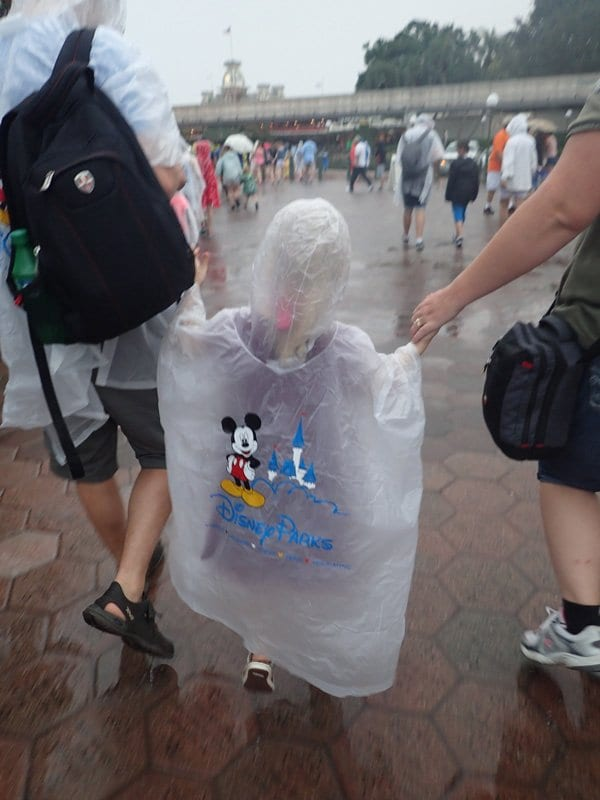 disney world florida ponchos on a toddler walking with parents in the rain