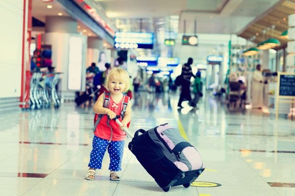 toddler at the airport bringing along a suitcase