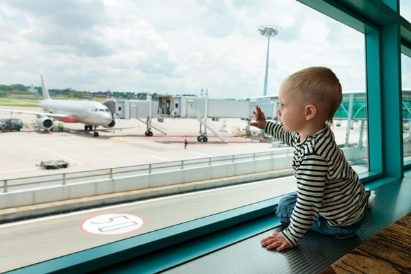 toddler watching planes at the airport
