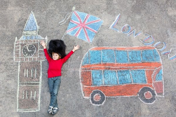 child laying on a chalk drawn picture of london with big ben and a london bus in the image