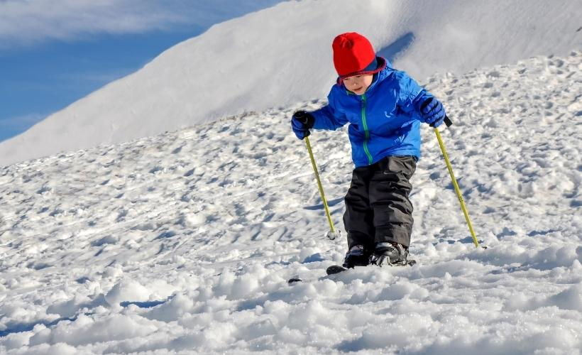 a child fully kitted out to join the family on their first ski trip together using the travelled so far packing list