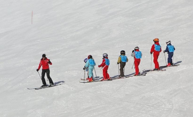group of kids with instructor on the slopes for ski school
